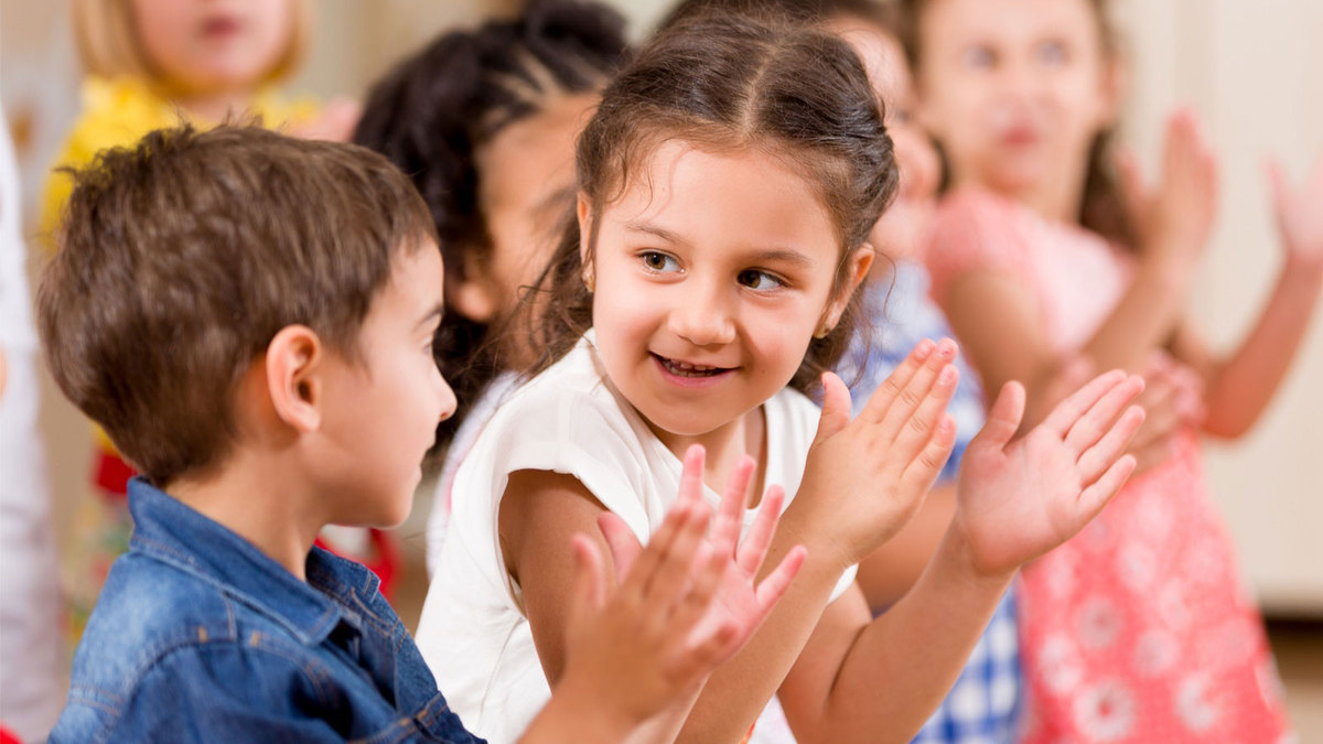 Group of young children clapping and singing