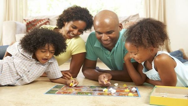 A family of four playing a board game on the floor.