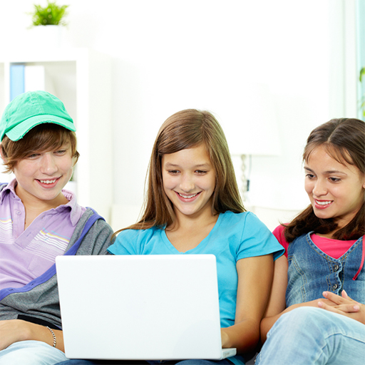 Three middle school children smiling while looking at a laptop