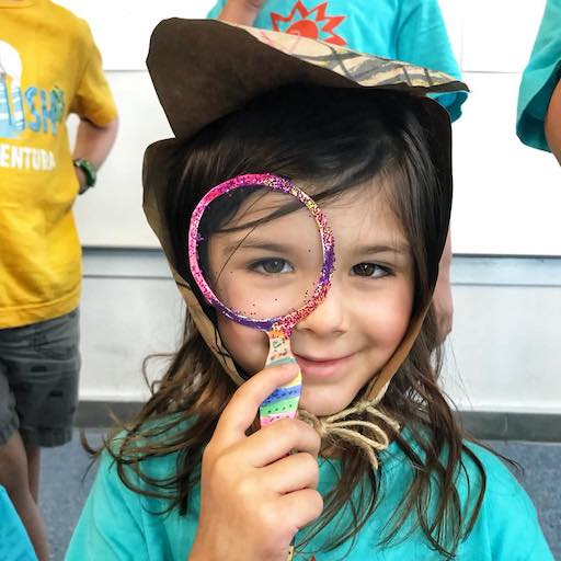 Child holding magnifying glass in front of face